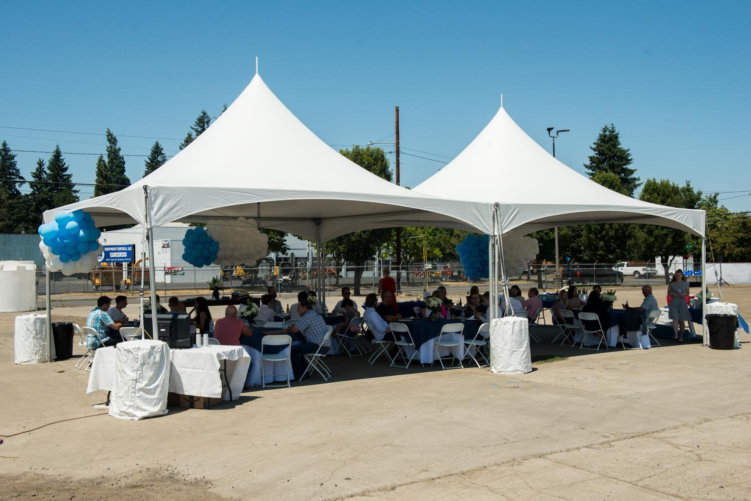 Groundbreaking attendees having lunch under a tent